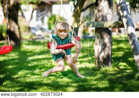 Happy Little Preschool Girl Having Fun On Swing In Domestic Garden. Healthy Toddler Child Swinging O