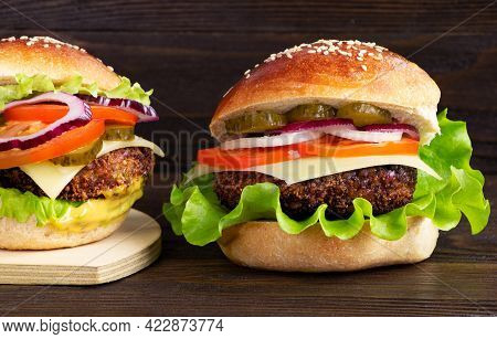 Cheeseburger On A Wooden Background. Hamburger With Cheese. Burger Isolated. Tasty Dinner. Copy Spac