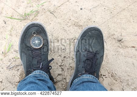 Classic Round Compass On Foot Against Background Of Sand In Summer On Camping Trip As Symbol Of Tour