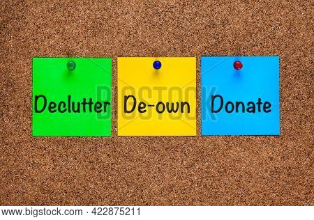 Three Colored Notes On Corkboard With Words Declutter, De-own, Donate. Close-up