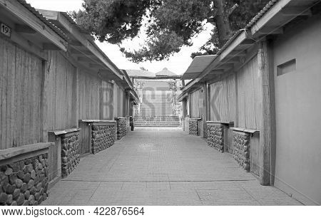 Diminishing Perspective View Of An Alley With Country Buildings In Monochrome