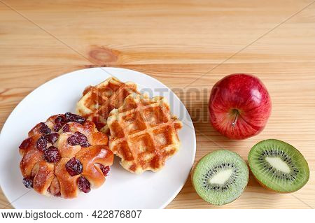 Plate Of Belgian Waffles And Raisin Bun On Wooden Table With Apple And Cut Kiwi Fruit With Copy Spac