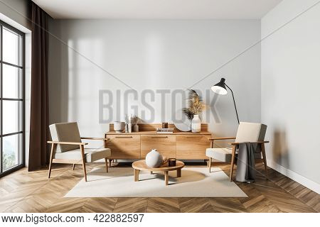 White Living Room Interior With Two Chairs And Commode With Art Books On Parquet Floor, Lamp And Win