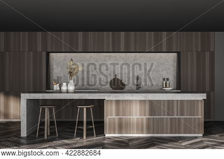 Interior Of Stylish Kitchen With Gray And Wooden Walls, Dark Wooden Floor, Bar With Stools And Cupbo