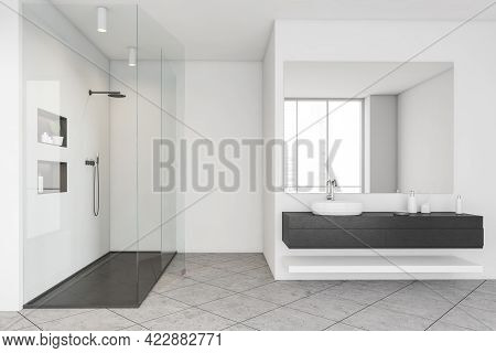 White Bathing Room Interior With Glass Shower, Washbasin With Gels And Bottles, Front View. Grey Til