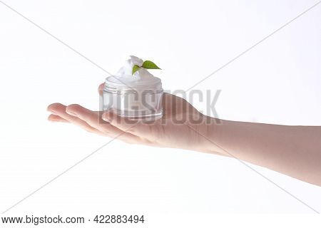 Beautiful Female Hand Holding A Jar Of Cream On A White Background Isolate, Skin Care Concept Of Moi