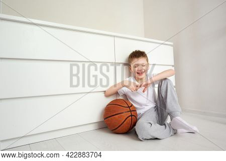 The Boy Closed His Eyes With Laughter Sitting On The Floor At His White Room, With A Basketball Near