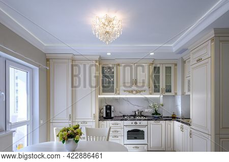 Modern large cream colored luxurious kitchen and dining room in studio apartment interior