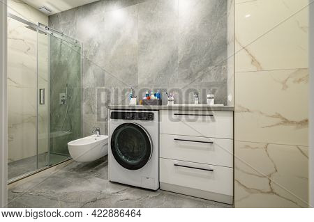 Modern luxury marble bathroom with toilet seat, sink, washing machine and glass walk-in shower cabin