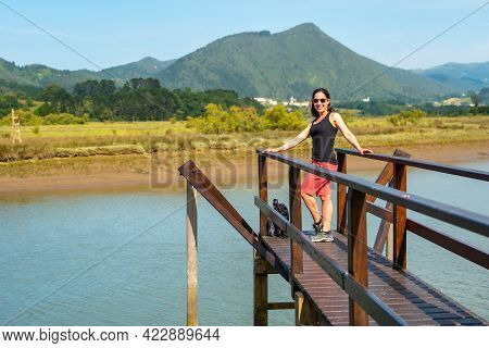 A Young Woman Enjoying The Scenery From The Wooden Piers Of The Urdaibai Marshes, A Biosphere Reserv