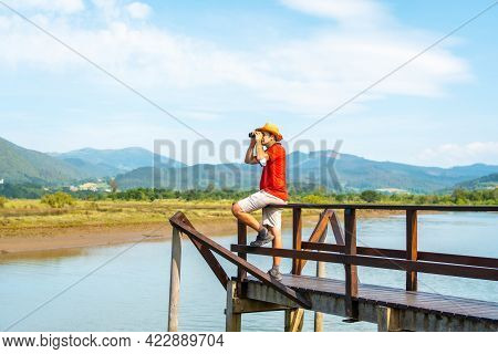 Watching Birds With Spyglasses From The Wooden Piers Of The Urdaibai Marshes, A Biosphere Reserve In