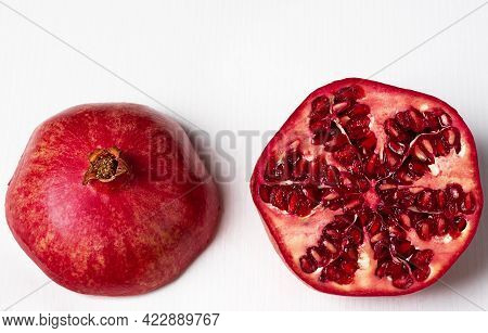 Two Halves Of A Pomegranate On A Light Wooden Background. Fruit Cut In Half