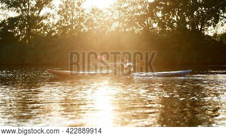 Young Man Holding A Paddle, Kayaking In A Lake Surrounded By Nature At Sunset. Kayaking, Travel, Lei