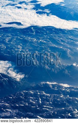 View From Airplane To Clouds And Land. Aircraft Flying Over Norway Scandinavia.