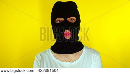 Close Up Of Unrecognizable Woman In Black Balaclava Shows Her Tongue On Yellow Background. Unknown F