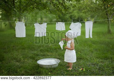 A Child Cheerfully Launderes His Clothes In The Basin.spray Water And Foam From Washing Clothes. Gir