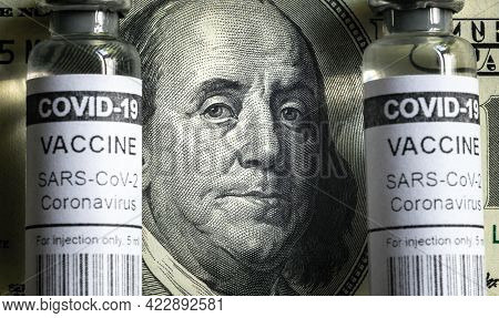 Vaccine Vials From Covid-19 And Dollar Bill, Franklin Portrait On Us Money Banknote And Coronavirus
