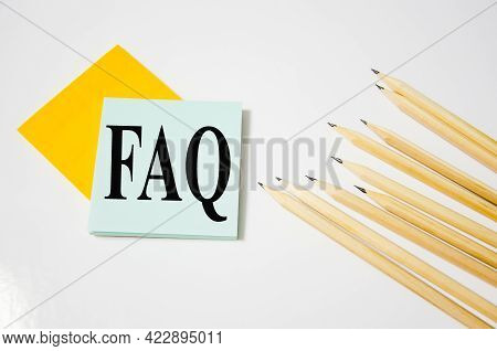Faq Word Written On A Yellow Piece Of Paper And White Background With Pencils Lying Next To It