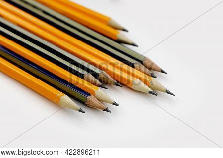 Few Sharply Sharpened Pencils Of Different Color On The White Table