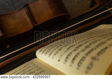 Selective Focus Of A Music Score Supported On A Music Stand Together With A Musical Bow And A Wooden