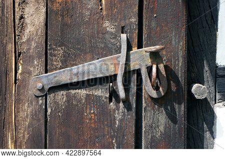 Ancient door latch on old wooden door in Koszalin, Poland.