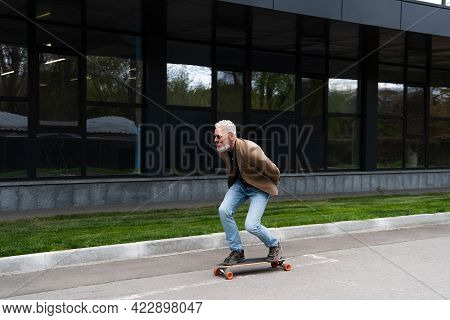 Full Length Of Happy Middle Aged Man In Sunglasses Riding Longboard Outside