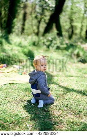 Little Girl In Overalls Kneels On A Green Lawn