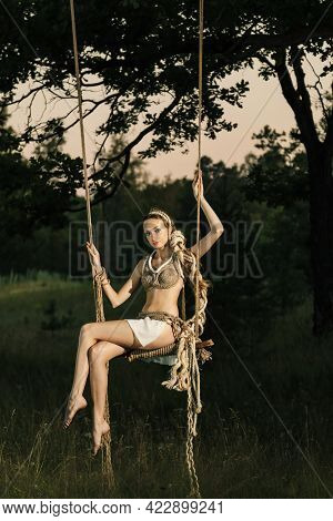 A Fairy Tale Fairy, A Forest Nymph In An Improvised Costume Made Of Hemp Rope, Swings On A Swing In