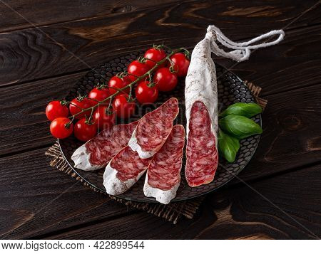 Fuet Catalan Sausage Slices And Bunch Of Fresh Cherry Tomatoes On A Black Plate Over Rustic Black Wo