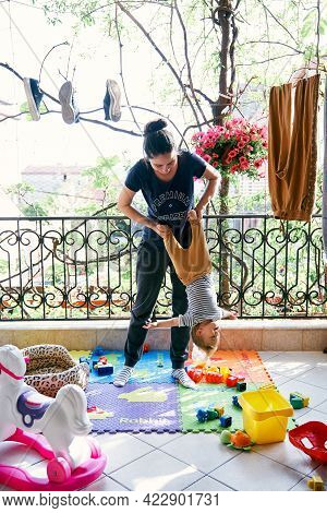 Mom Stands On The Rug On The Balcony And Rocks The Little Child Upside Down