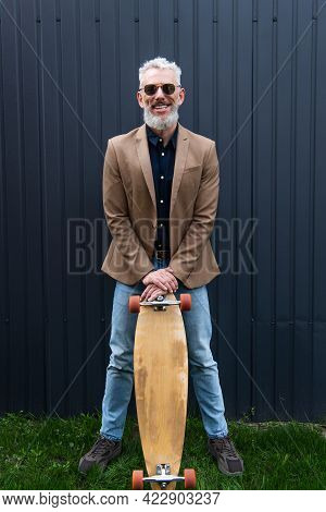 Full Length Of Happy Middle Aged Man In Sunglasses Holding Longboard Outside
