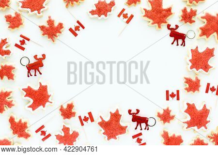Canada Day Border Including Mini Canada Flags, Moose Key Chains And Canada Flag Sugar Cookies.