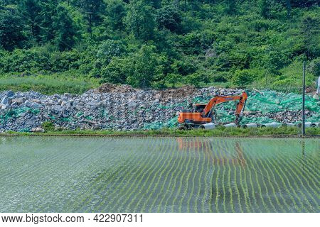 Seochon, South Korea; June 2, 2021: Wheeled Backhoe In Front Of Rocks Pile With Rice Paddy In Foregr