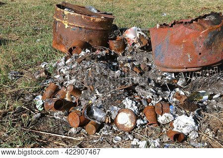 Ashes And Charred Debris Lay Exposed On The Ground Next To Two Burn Barrels.