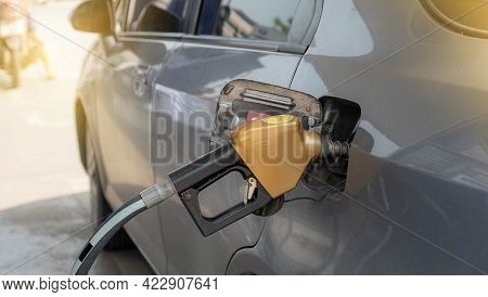 Golden Nozzle Pump Gun Petrol From Oil Pump In The Car Tank To Refueling.
