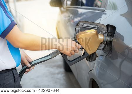 Worker Hand Holding Golden Nozzle Pump Gun Petrol From Oil Pump In The Car Tank To Refueling.