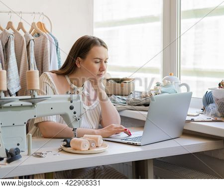 Young Focused Woman Atelier Owner Working On Laptop While Sitting At Workplace With Sewing Machine,