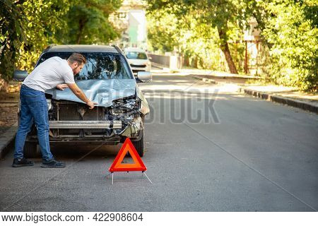 Man Driver Looking On Smashed Broken Car In Accident. Red Emergency Stop Triangle Sign Afore Destroy