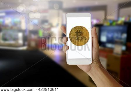 Hand Holding Phone With Digital Bitcoin Cryptocurrency To Pay, E-commerce And Blockchain Concept