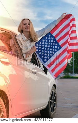 Young Millennial Blonde Woman Looking From Car With American Flag. Flag Of The United States In Her