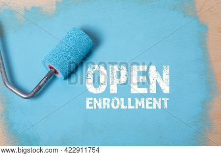 Open Enrollment. Paint Roller With Blue Paint On A Wooden Surface