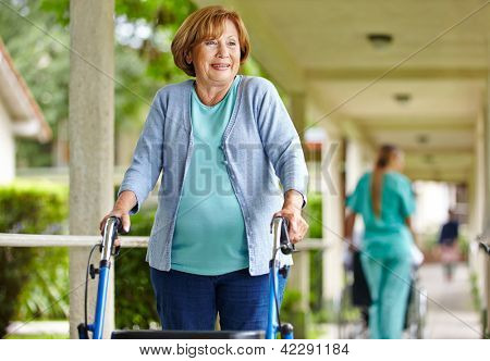 Old happy woman with walker on a stroll in the park of a nursing home