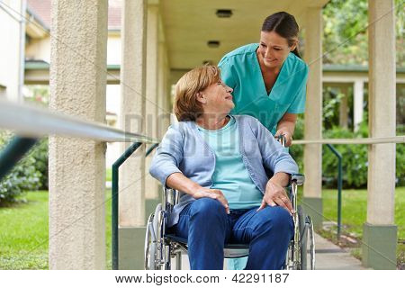 Senior woman in wheelchair talking to a nurse in a hospital garden