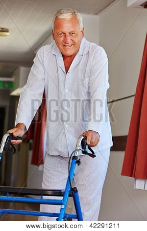 Senior man walking with a walker throough the floors of a nursing home