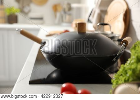 Frying Pan With Lid On Cooktop In Kitchen