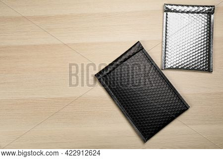 Two Padded Envelopes With Bubble Wrap On Wooden Background, Flat Lay. Space For Text