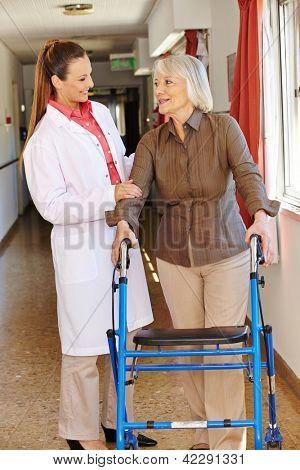 Nurse talking to senior patient with walker in hospital