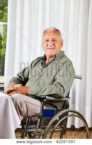 Smiling senior sitting in a wheelchair in a nursing home