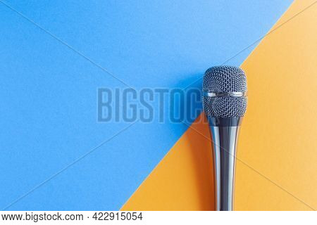 Microphone On A Colorful Blue And Orange Geometric Background Close Up. Singing, Writing Music, Kara