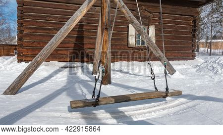 The Old Swing Was Made Of Unpainted Logs And Hung On Ropes From The Posts. Background - A Wooden Hou